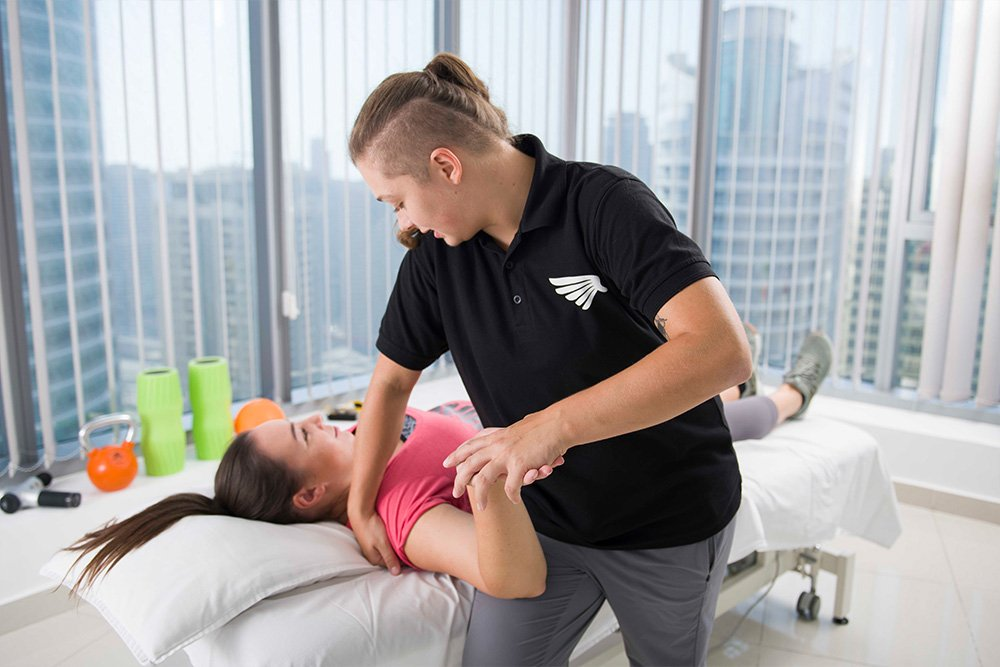 lady physiotherapy massaging patient's right shoulder