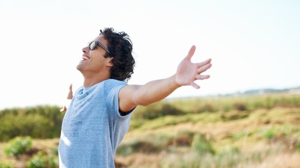 Gorgeous young man wearing shades and holding his arms out happily while outdoors in a field